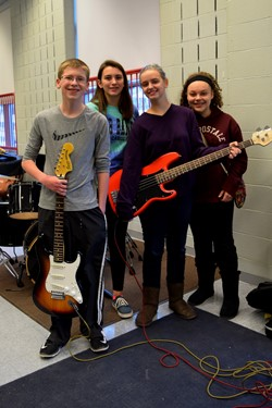 students holding electric guitars