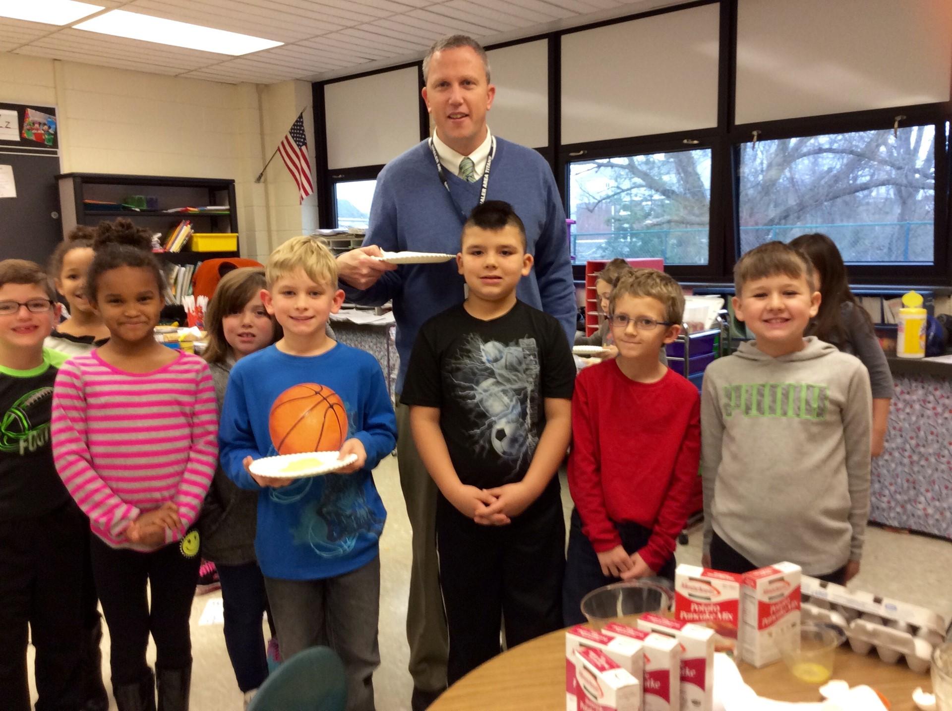 Mr. Aiken enjoys latke with second graders.
