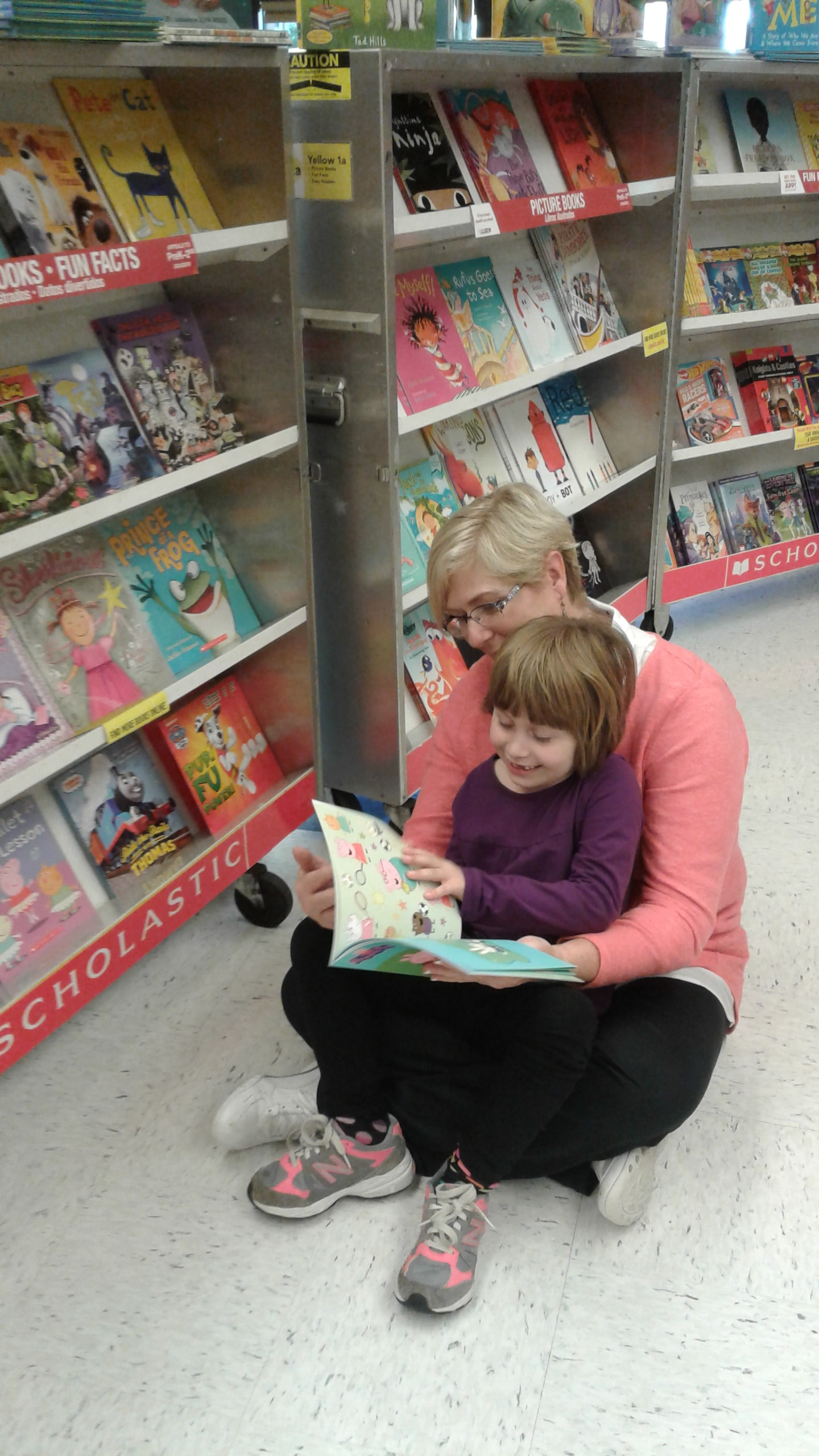 Librarian reading a book to a little girl at the book fair