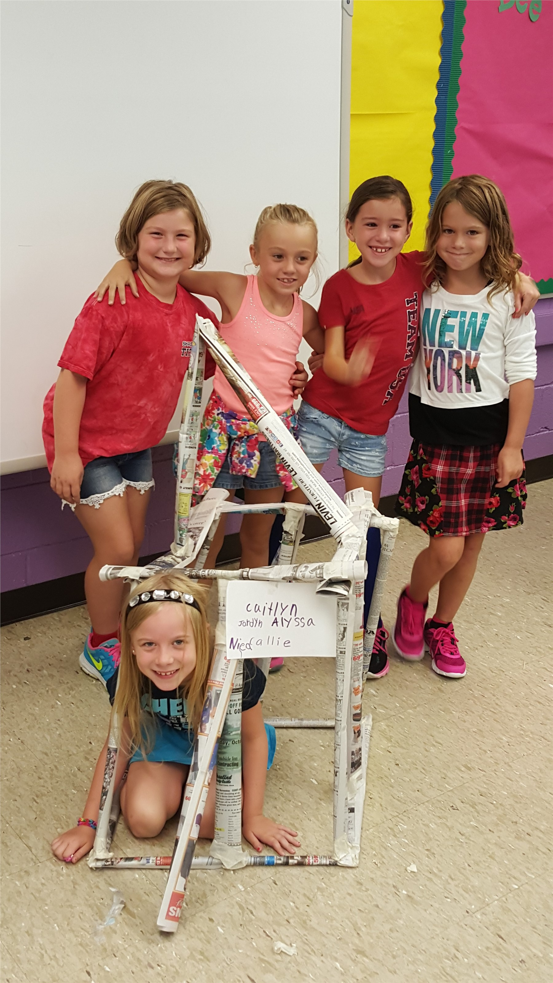 Students standing next to a three dimensional house that they created from newspaper rolls.
