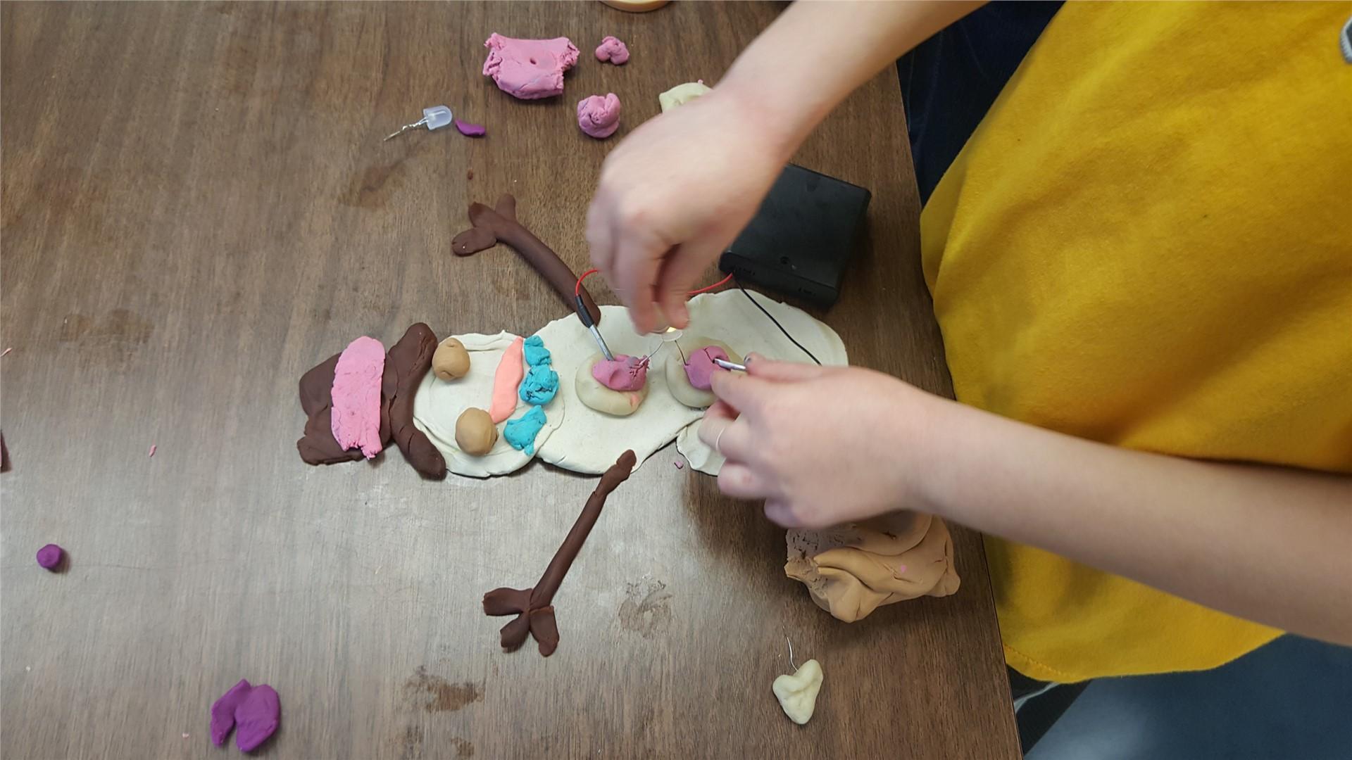 Hands creating snowman sculpture