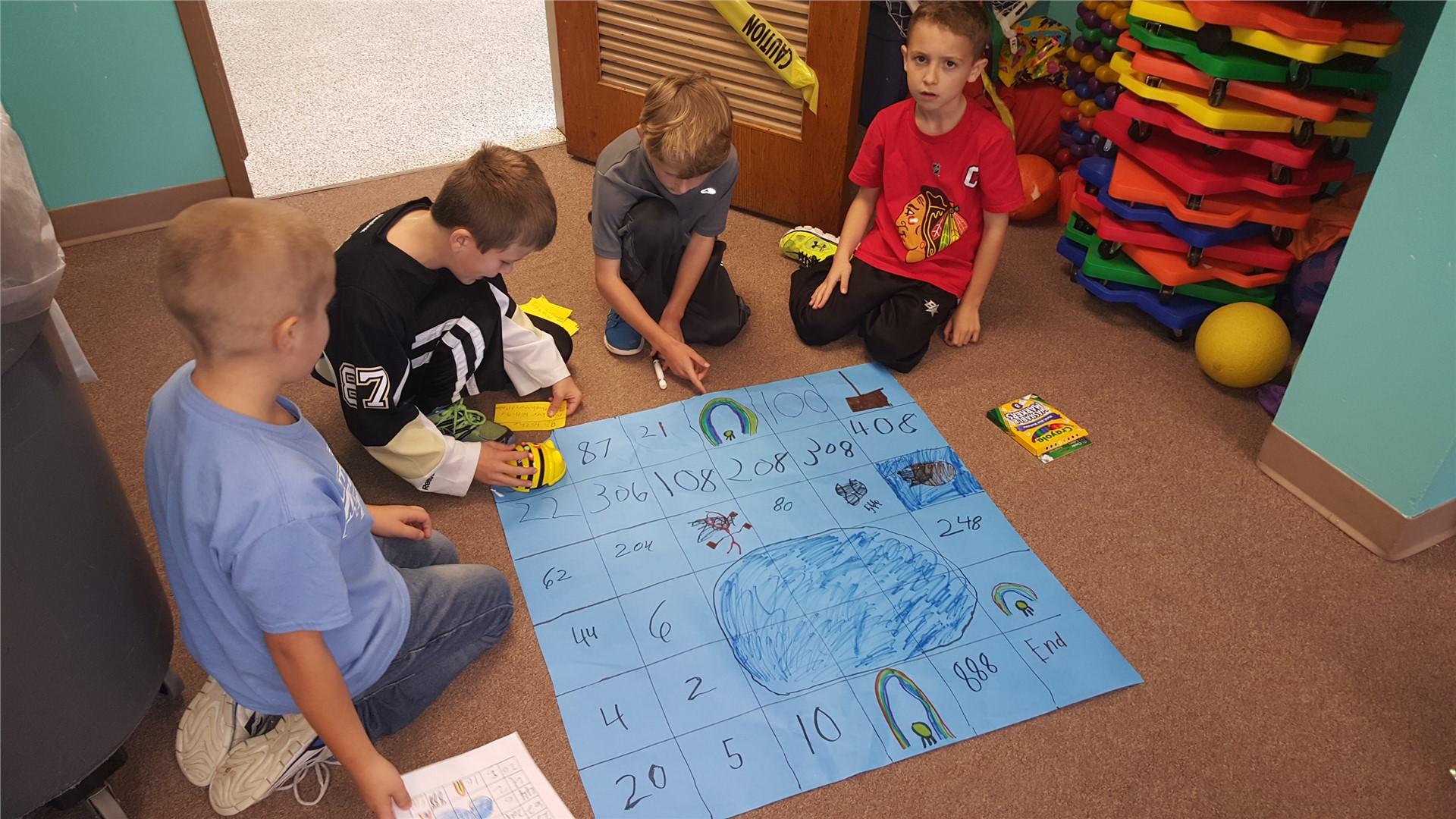 Students around puzzle on floor