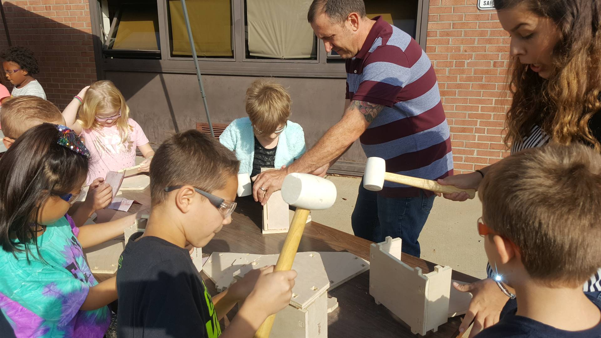 Students using mallets to hammer toolbox together.
