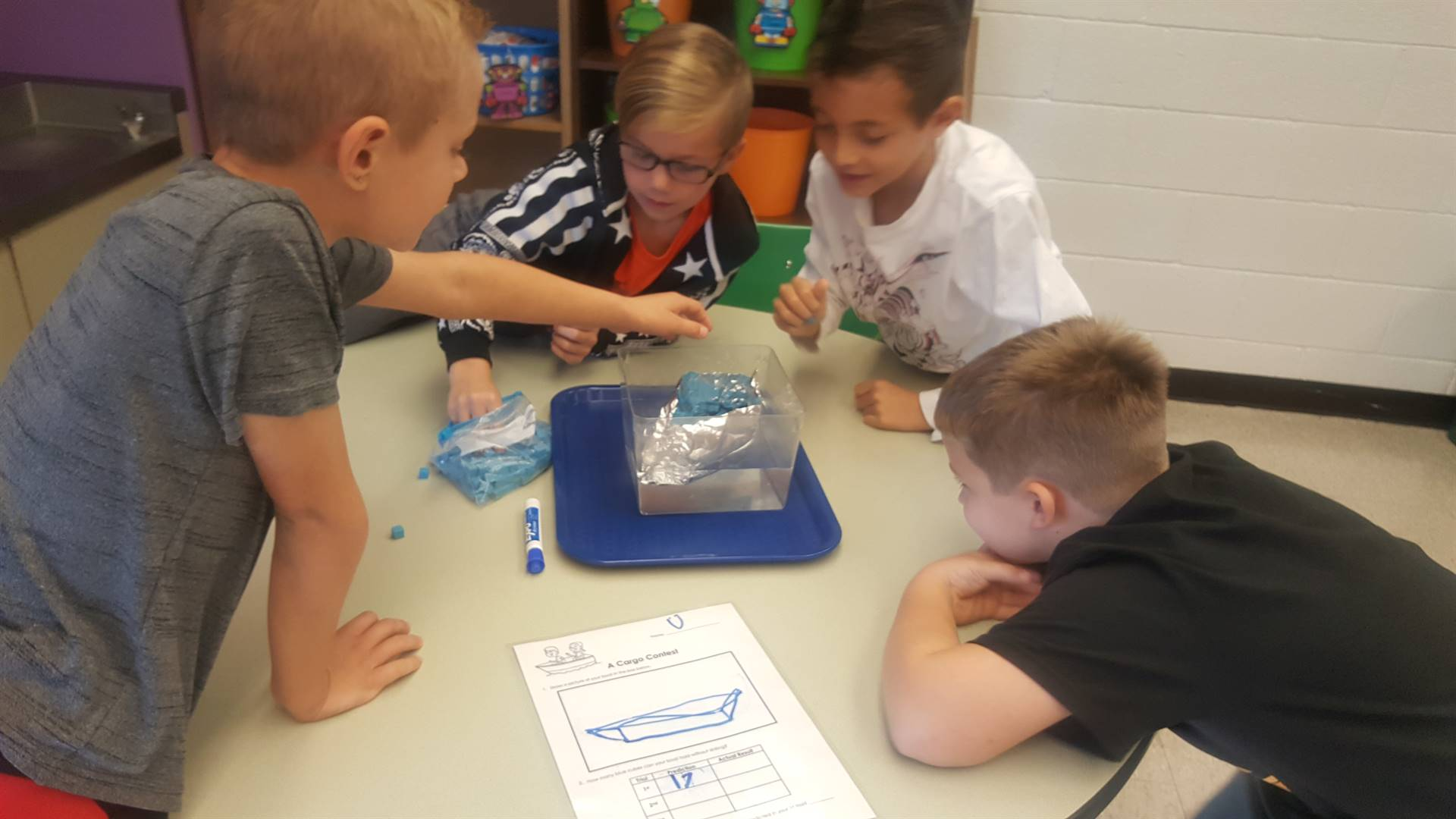 Students floating a foil boat in the water and adding small blue blocks to the boat.