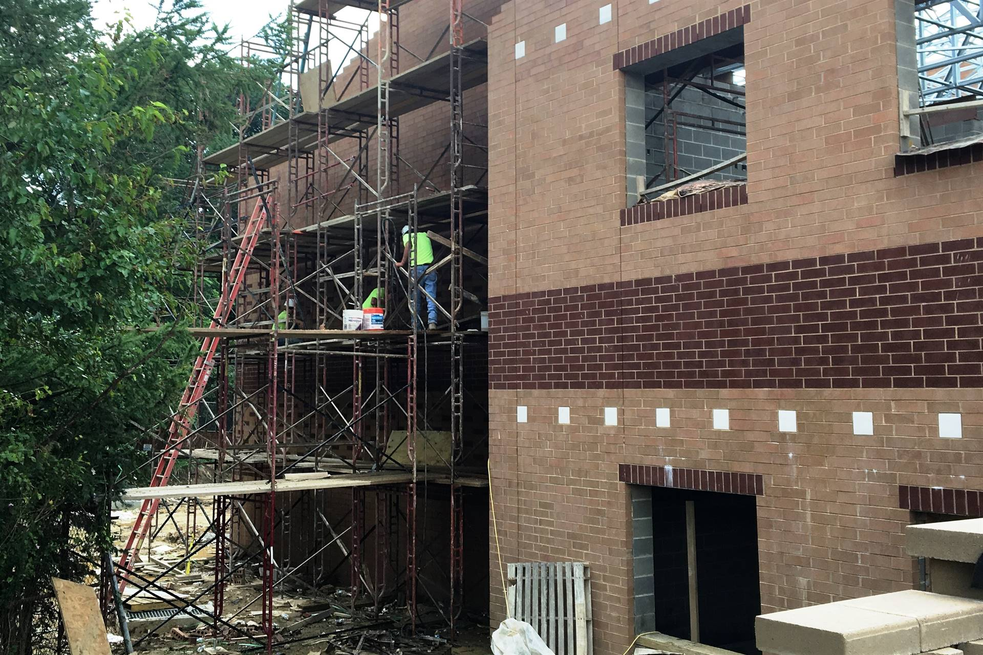 Workers installing exterior bricks at Scott Primary construction site