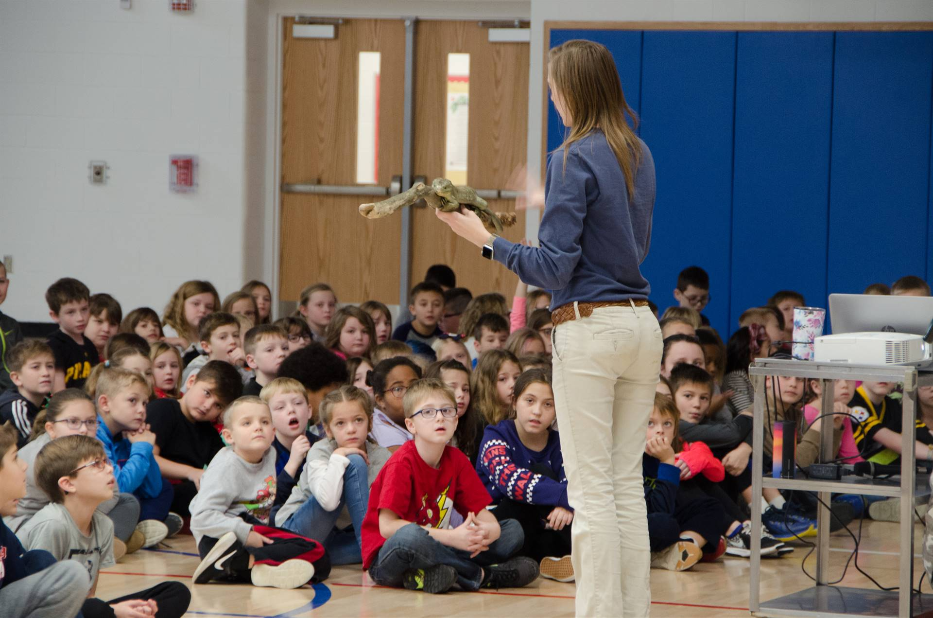 Woman shows rainforest animal to students
