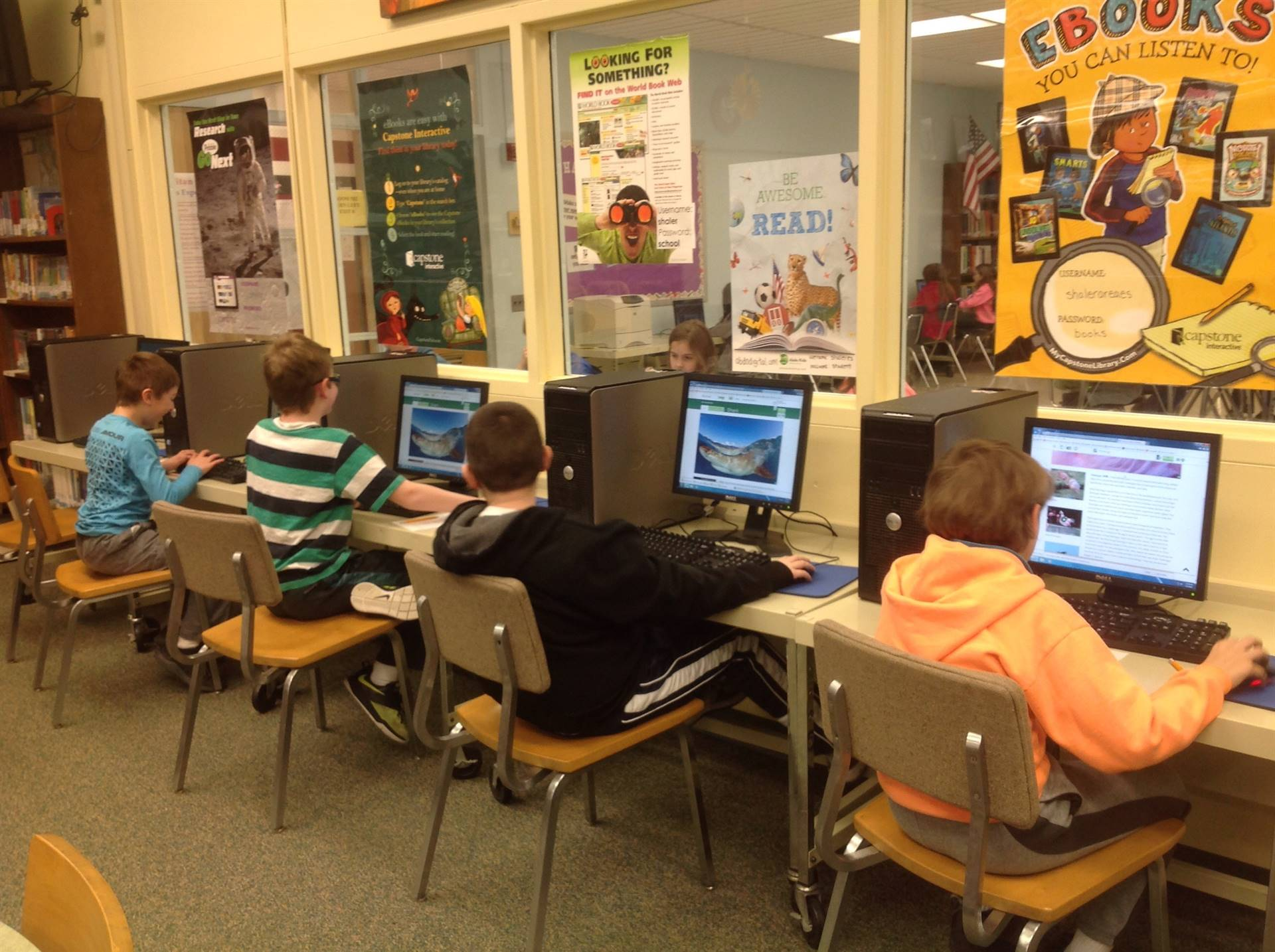 four fourth grade boys using computers for research