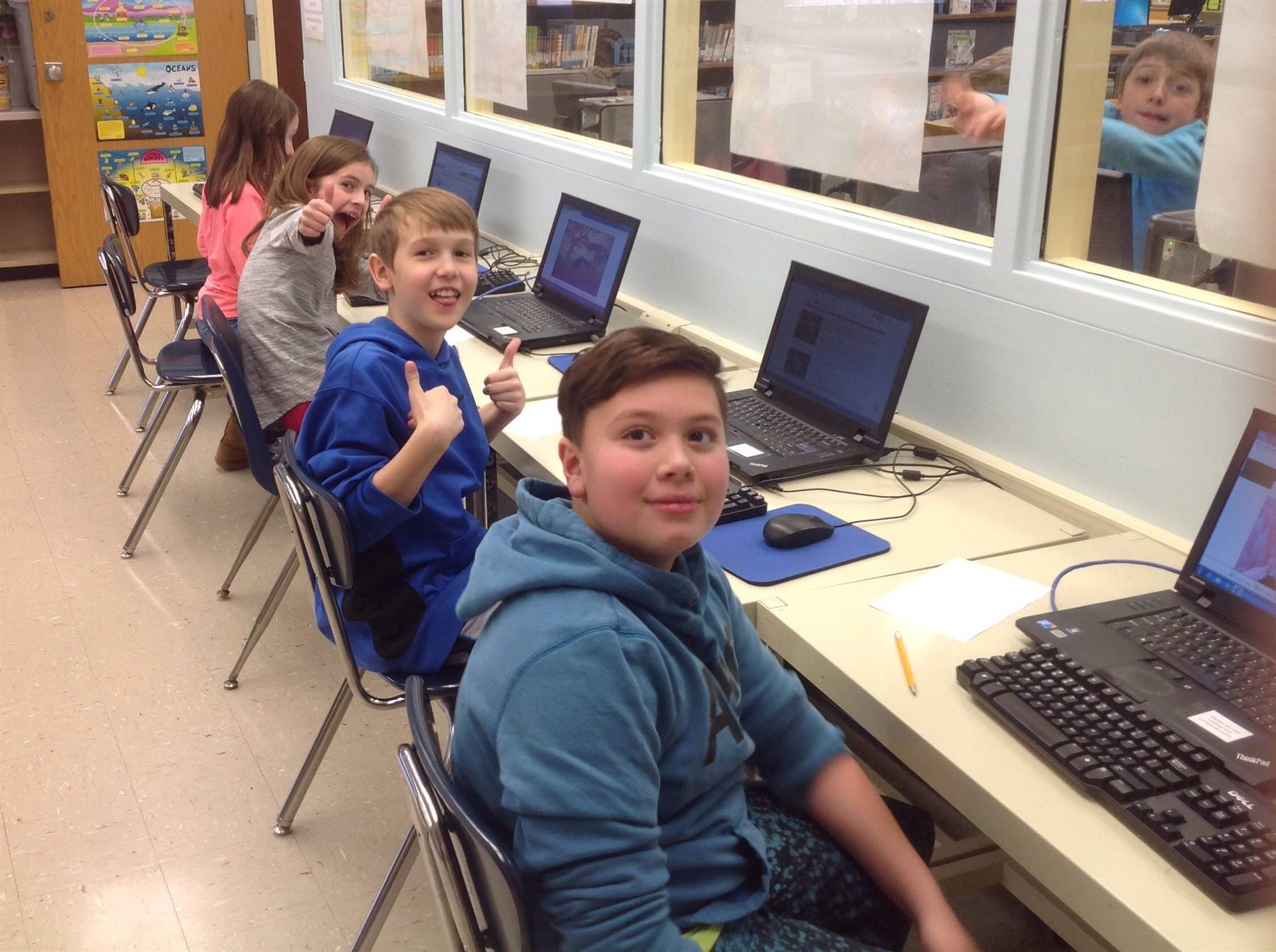 a group of fourth graders using the computers for research