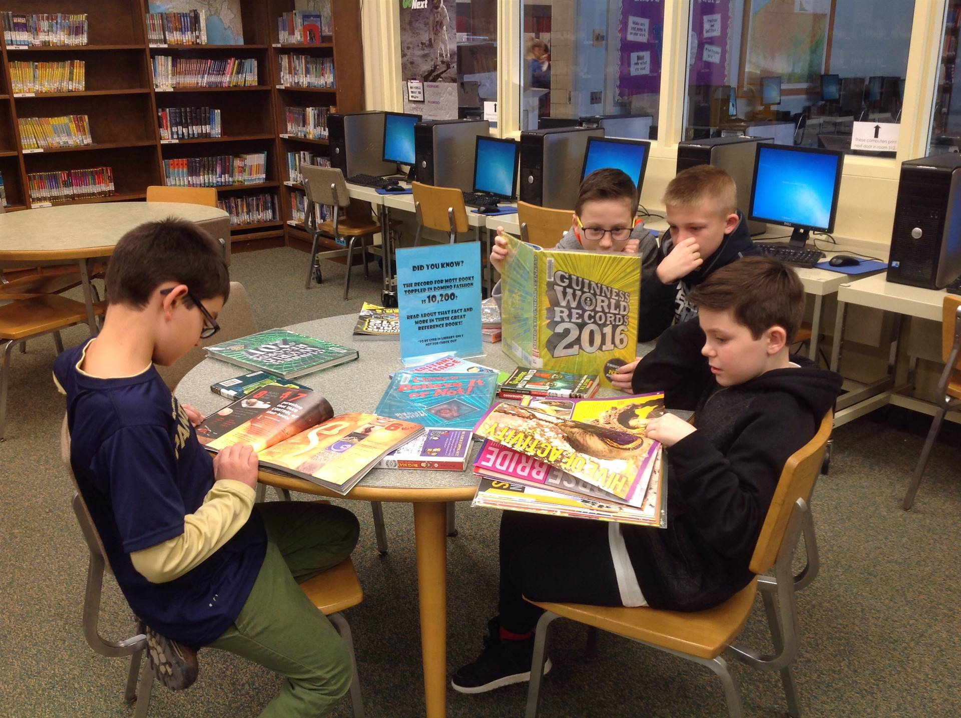 a group of boys look up facts in reference books