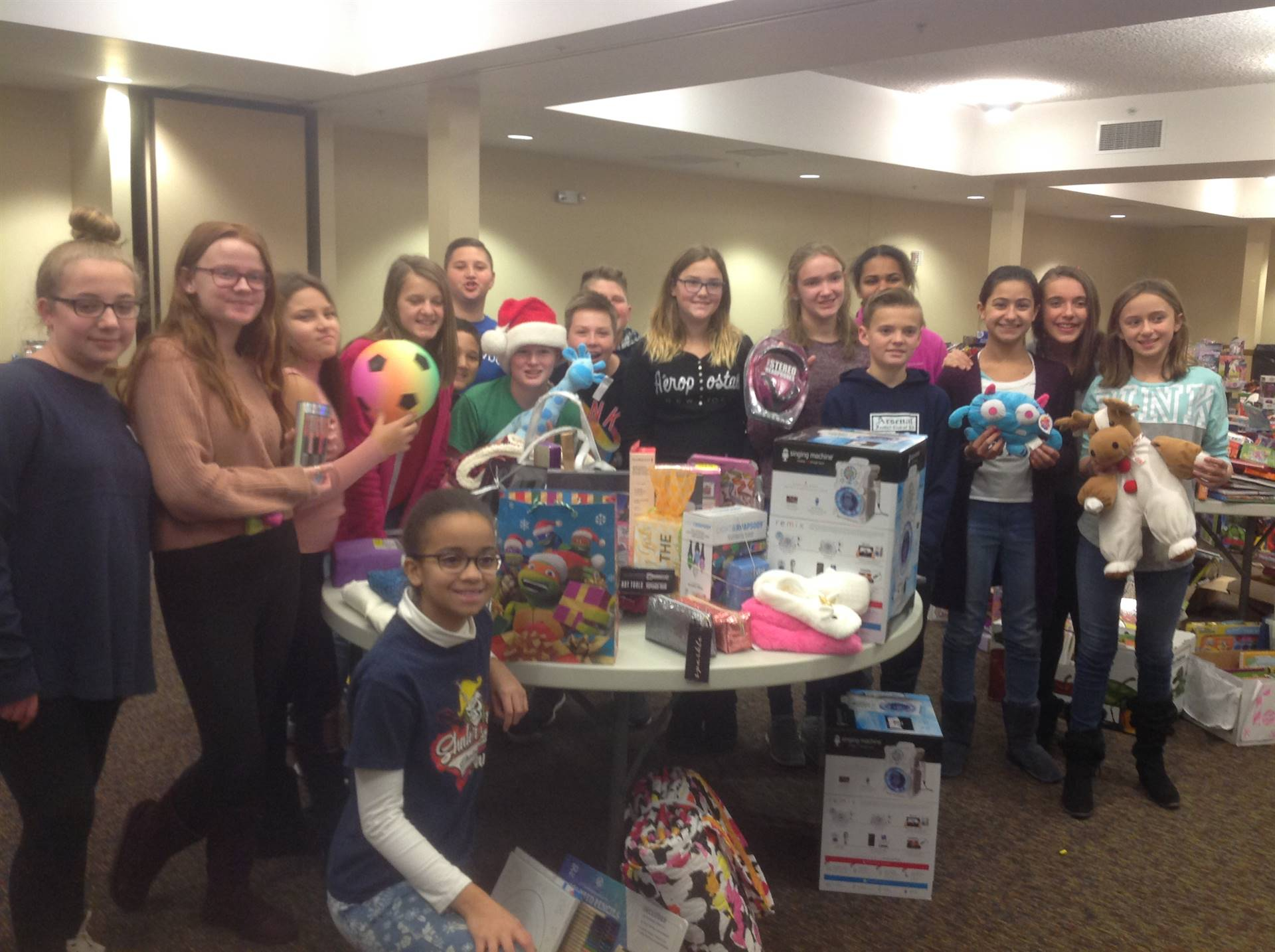 17 students posing with collected toys from SAES school toy Drive