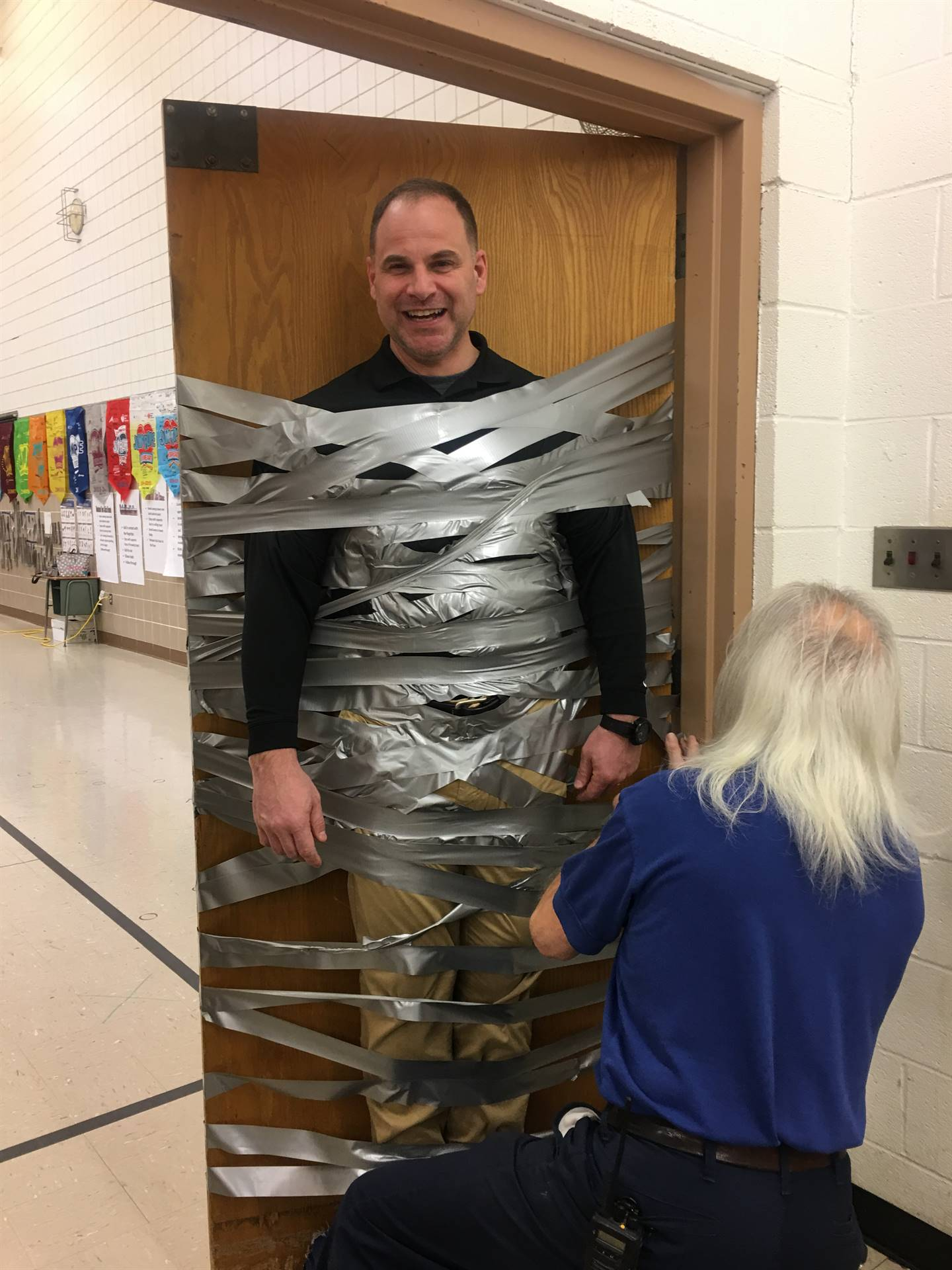 Mr. Rojik gets taped to the door as a reward during the Pennies for Patients  fundraiser