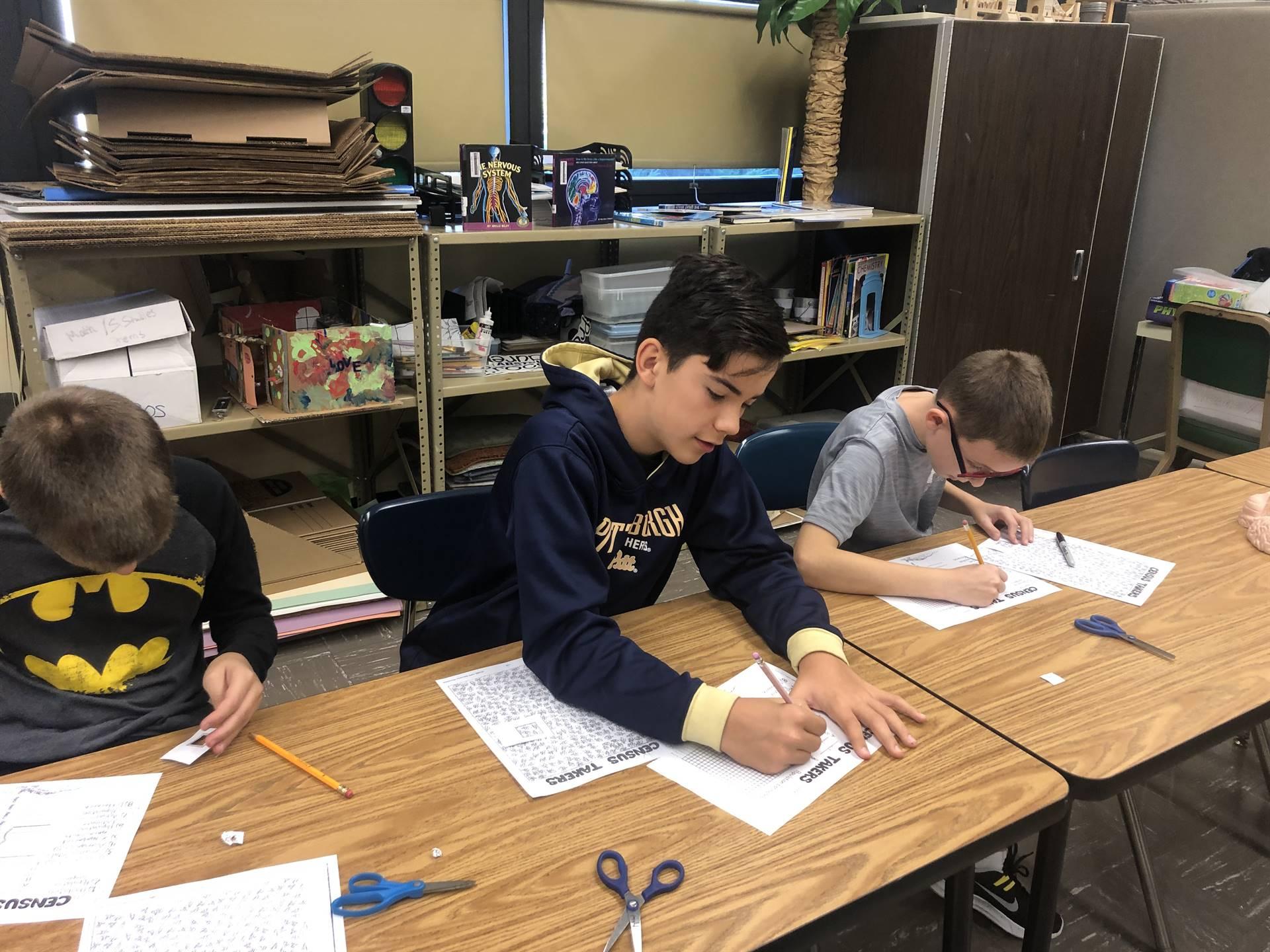 3 6th grade boys applying math in ant sampling activity