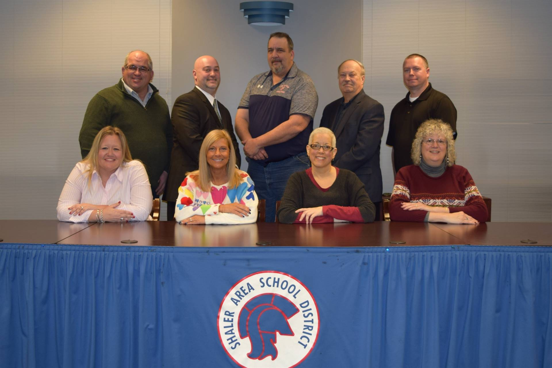 nine school board members at a table