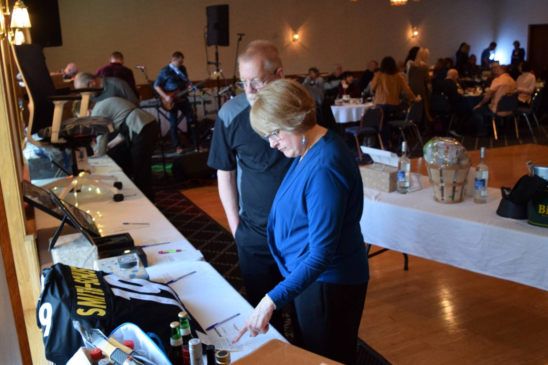 Two people looking at table of auction items