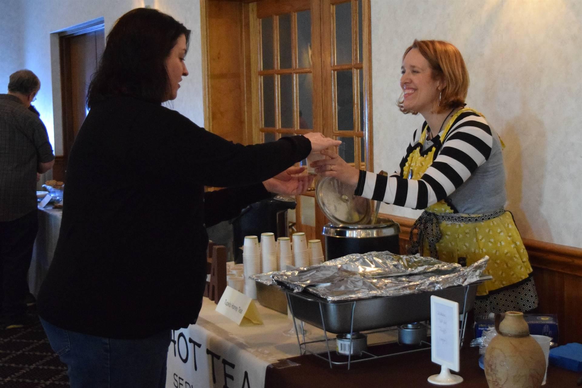woman serving soup to woman