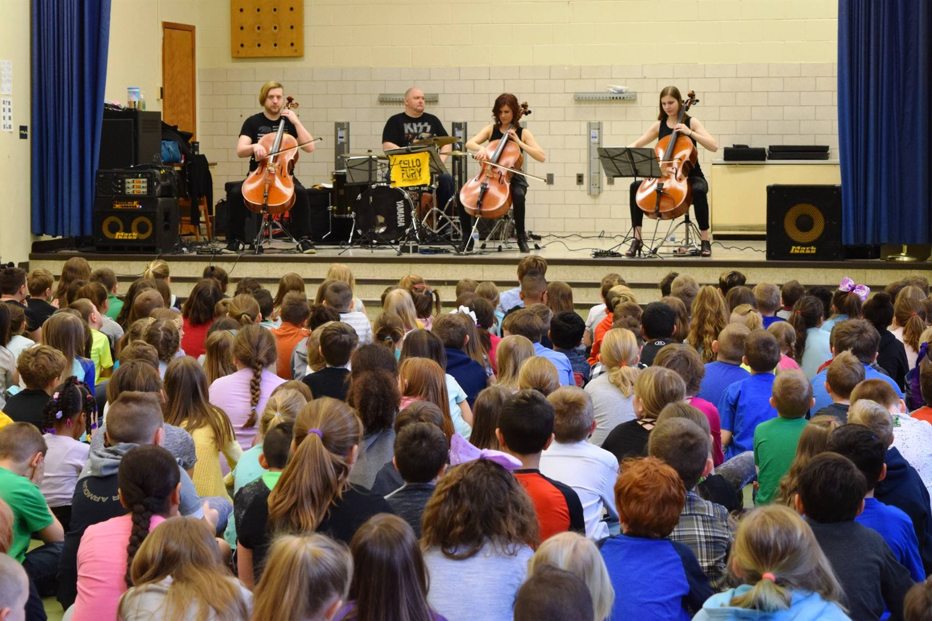 Cello Fury band playing a concert for students