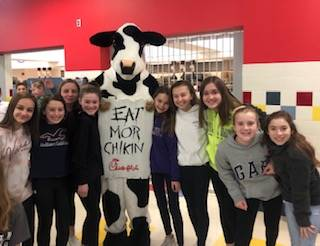 Chick fil a cow mascot and 7 girls posing for a picture during lunch.