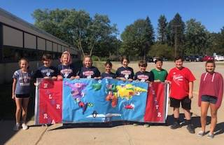 Homecoming Banner with 10 6th Grade Students who Created It