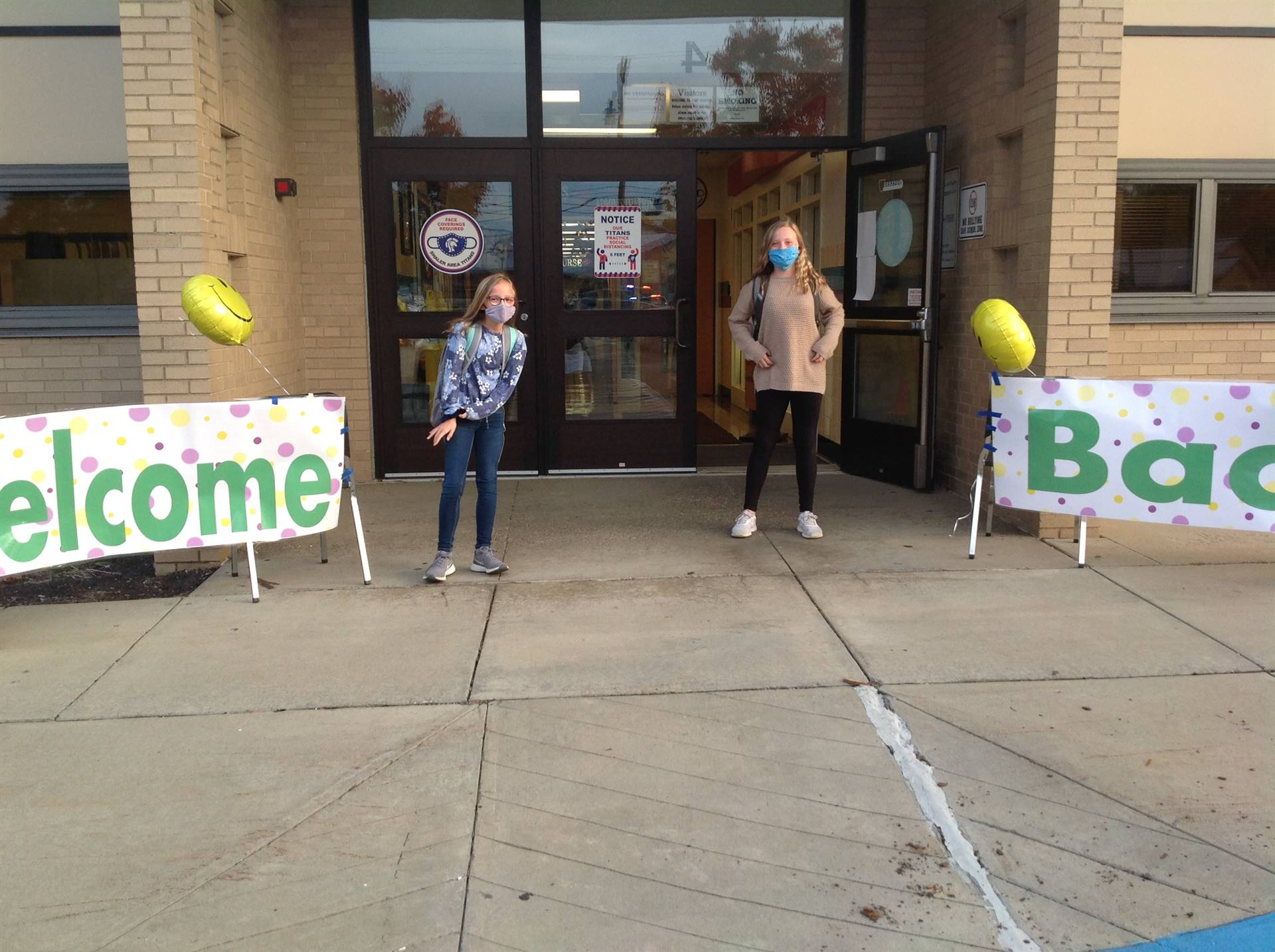 Welcome Back Sign and 2 Students