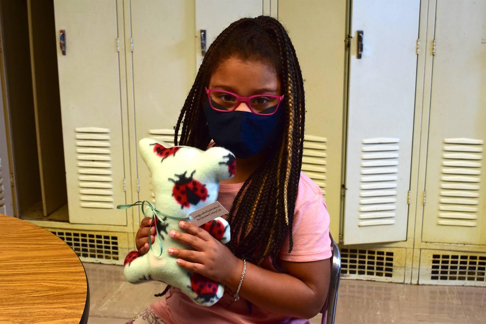 Kindergarten student holding a caring bear
