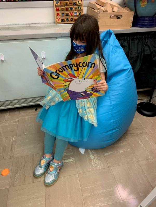 Kindergarten student reads a book