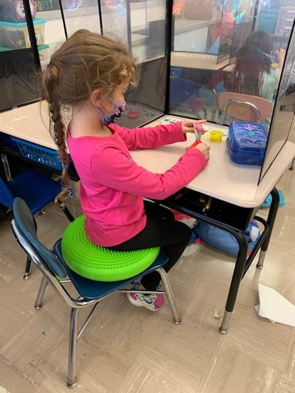 Kindergarten student at her desk