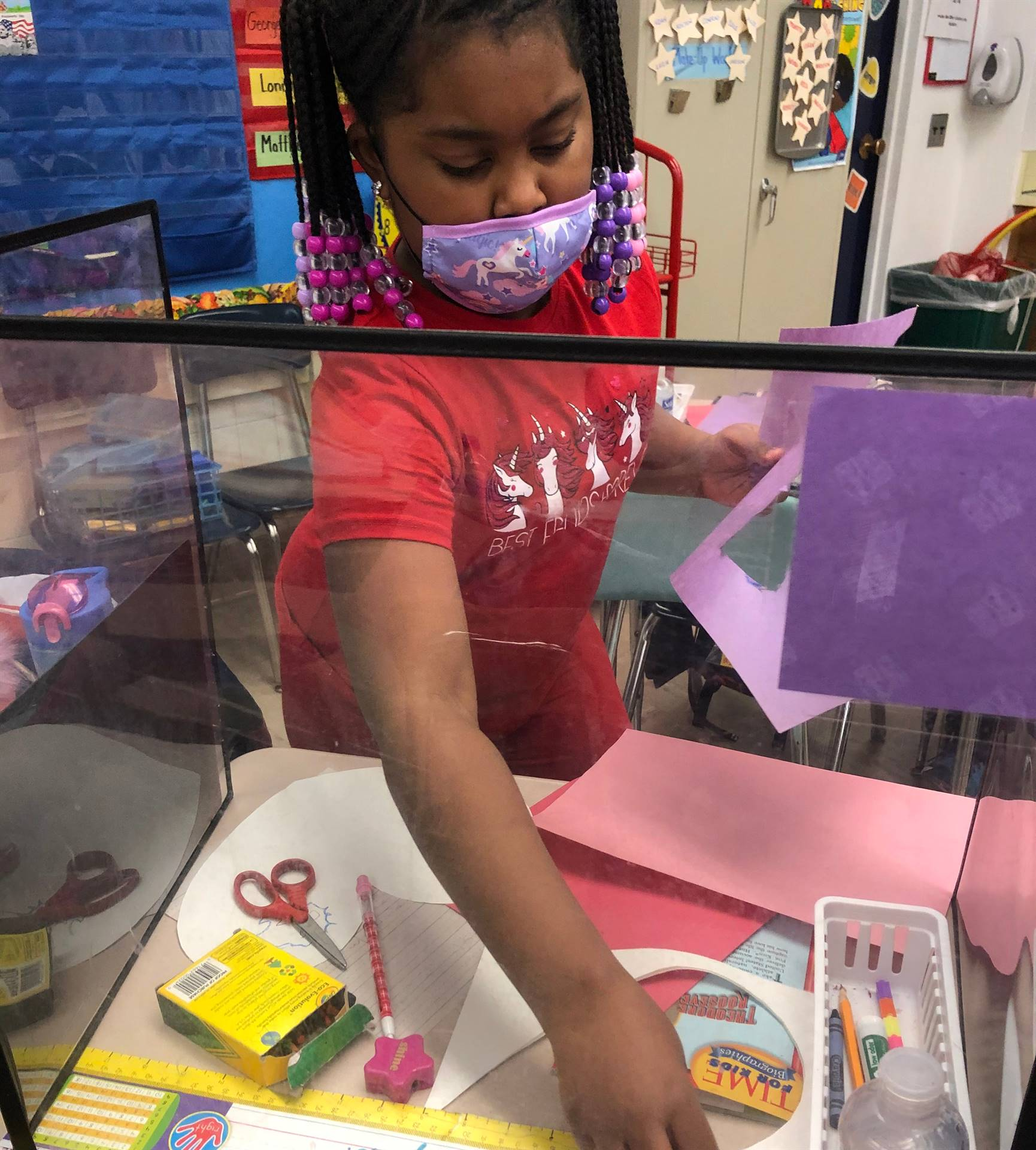 student decorating Valentine's Day craft