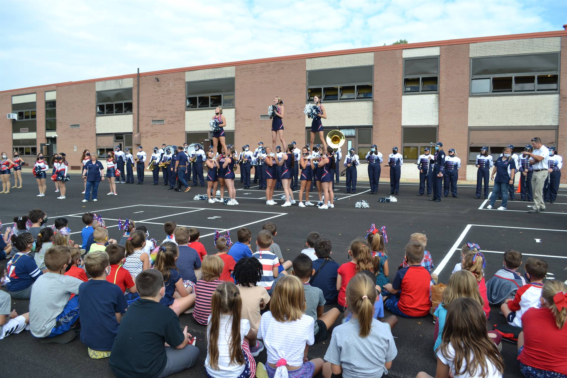 Cheerleaders cheering as students watch during Pep Rally Day