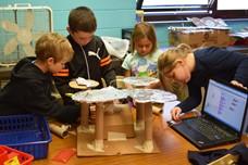 Four students building a cardboard drum set