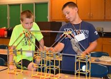 Two boys standing behind a model bridge