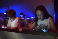 Two students looking at iPads in a simulator space ship